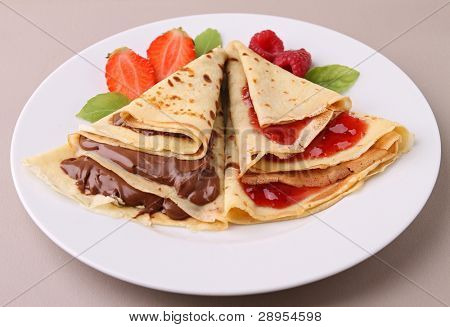 plate of pancake with chocolate and fruit