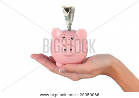 Closeup of a woman's hand holding a pink piggy bank with a dollar bill stuck in the top slot. Horizontal format over a white background.