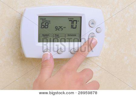 Primer plano de una mano de Mules, ajuste la temperatura ambiente en un moderno termostato programable.