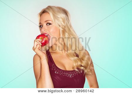 Sexy blonde woman biting into a juicy fresh red apple, studio portrait on blue