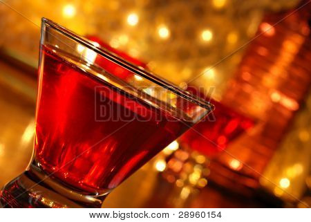 Tilted composition of red cocktail drink on bar with additional drinks, a bottle and defocused golden lights in background.  Macro with shallow dof.