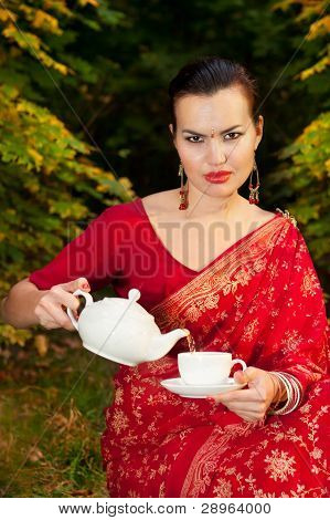 Woman In Indian Sari With Teapot And Cup Of Tea
