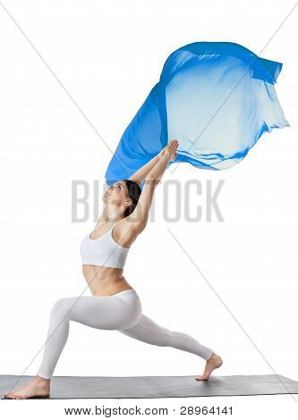 woman doing yoga asana with blue flying fabric