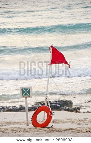 Red Warning Flag And Lifering On Stormy Beach