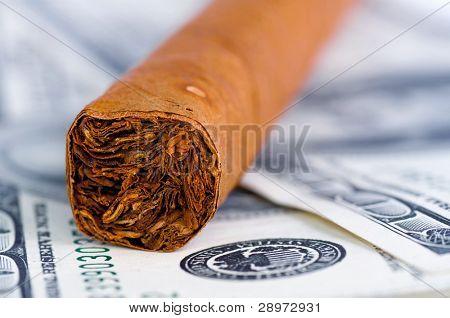 Close-up of cigar on the hundred Dollars bills