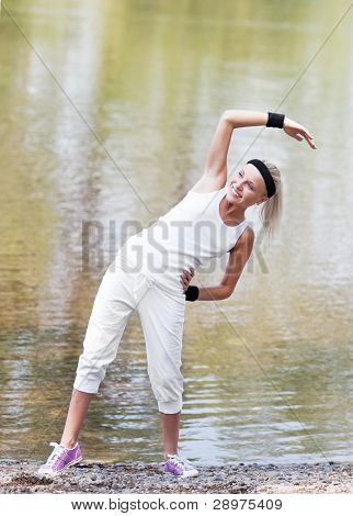 beautiful young  sporty woman jogging in the park and stretching her muscles by the pond on a warm summer day