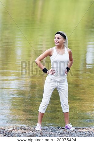 beautiful young  sporty woman jogging in the park by the pond on a warm summer day