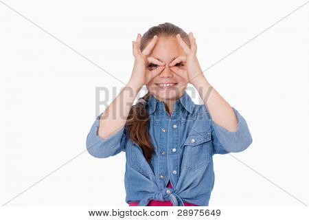 Girl with her fingers around her eyes against a white background