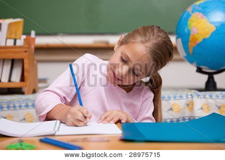 Happy schoolgirl writing in a classroom