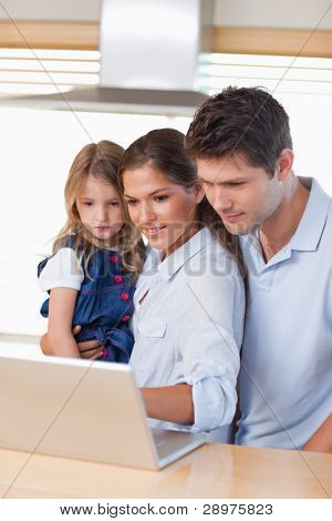 Portrait of a family using a laptop in their kitchen