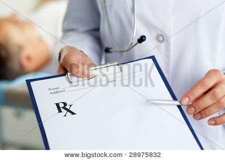 Hand of female doctor with pen pointing at clipboard