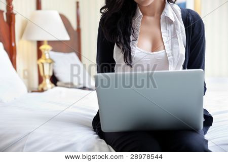 Cropped image of business woman using laptop while sitting on bed