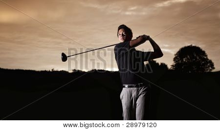 Close up professional golf player in black shirt teeing-off with beautiful sunset in background, front view.