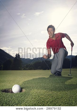 Male golf player in winner pose on green with putter as golf ball drops into hole.