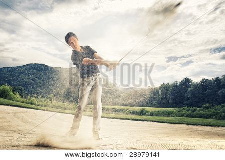 Male golf player in blue shirt and grey pants hitting golf ball out of a sand trap with sand wedge and sand caught in motion.