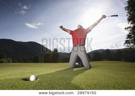 Male golf player on knees and arms raised with putter in hand in winner pose on golf green being overjoyed as golf ball drops into cup.