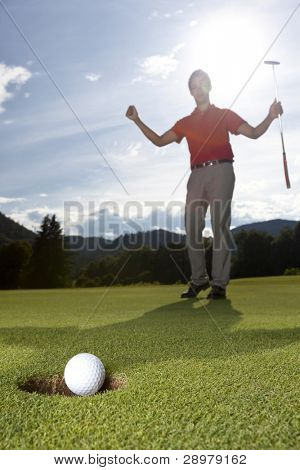 Male golf player cheering with arms raised and putter in hand on golf green as golf ball drops into cup.