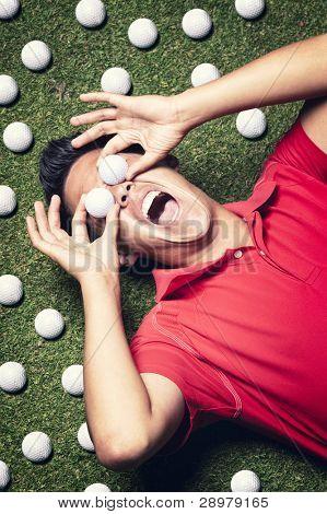 Junge Geschrei männlichen Golfspieler in rotes Hemd auf grün neben mehreren Golfbälle liegen und die