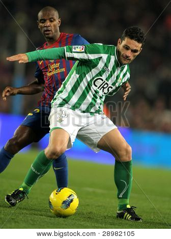 BARCELONA - JAN 15: Jorge Molina(R) of Real Betis vies with Eric Abidal(L) of FC Barcelona during the Spanish league match at the Camp Nou stadium on January 15, 2012 in Barcelona, Spain