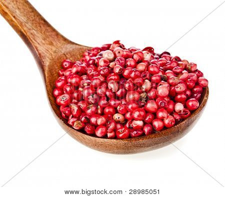 pink peppercorn  in a wooden spoon , on white background.