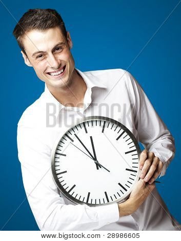 portrait of young man holding clock against a blue background