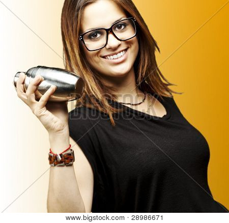 portrait of young woman shaking cocktail over orange background