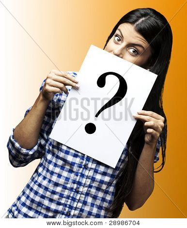 portrait of young woman with question paper on yellow background