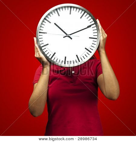woman holding clock in front of head against a red background