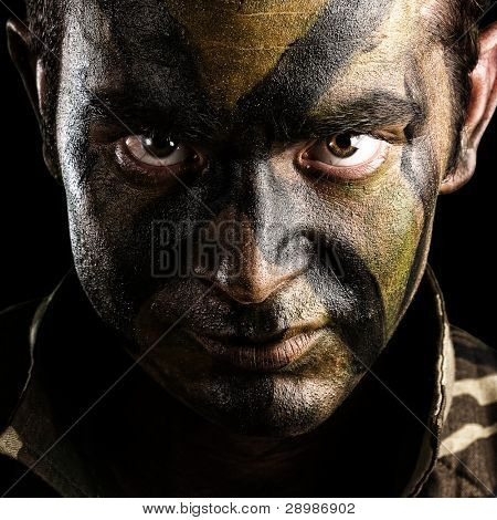 young soldier face with jungle camouflage paint on black background