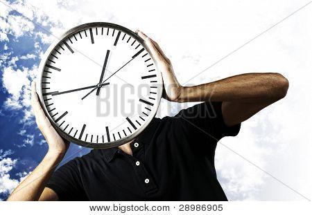 retrato de jovem segurando um relógio com suas mãos contra um fundo de céu nublado