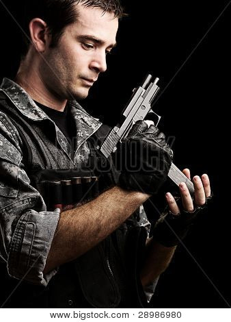 portrait of young soldier reloading his gun against a black background