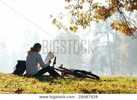 Woman Cyclist With Read The Map Sitting Among The Green Scenery