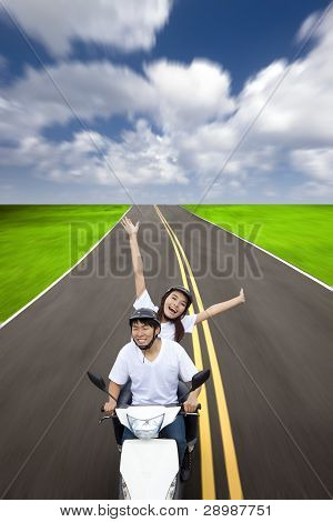 Happy couple having summer road trip on a scooter