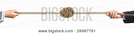 two hands pulling golden chain with twisted part on the center on the opposite side, isolated against white background