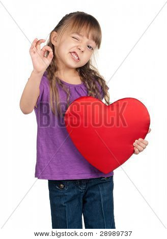 Portrait of little girl holding red heart and gesturing OK over white background