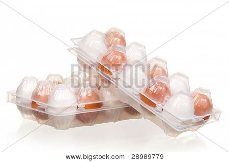 Brown and white eggs in the plastic box over white background