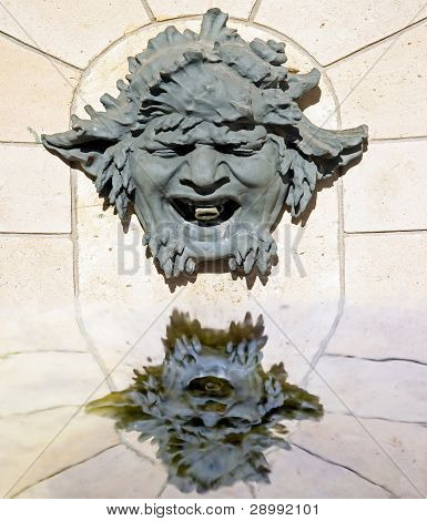 grotesque, mask, and its reflection in water