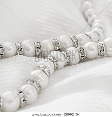 Pearls necklace with brilliant rings on a silk