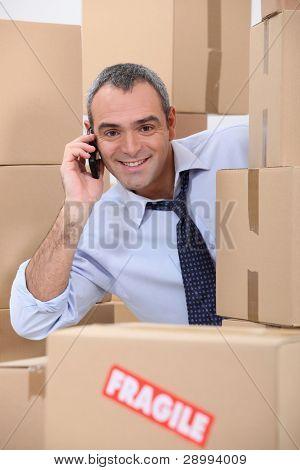 um funcionário de 40-45 anos de idade, chamando alguém em uma sala cheia de caixas de papelão