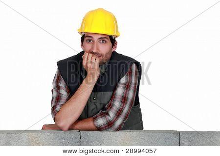 A mason biting his nails.