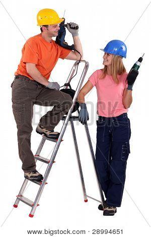 Male and female carpenters flirting