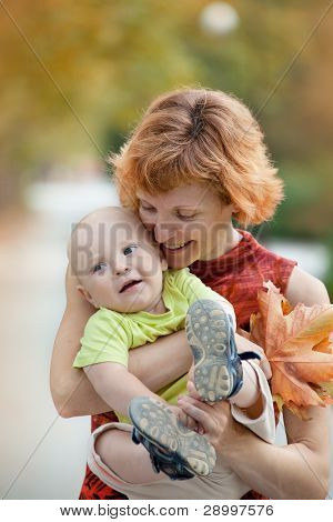 Young Mother And Son Walking In The Park