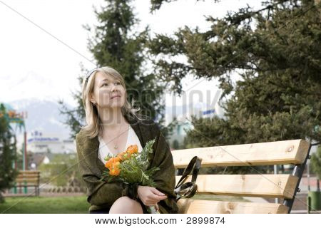 Women With Bunch Of Flowers Sitting At The Bench In Spring Park