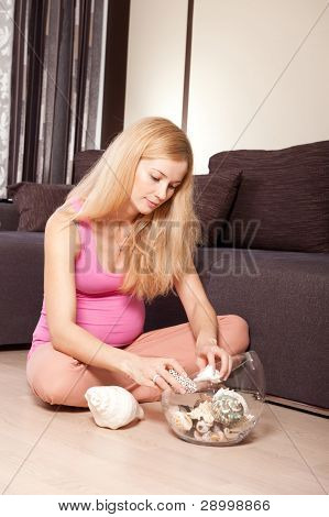 Pregnant Woman On The Floor With Seashells