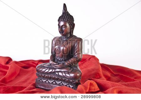 Side View Of Wooden Buddha Statue On Red Fabric