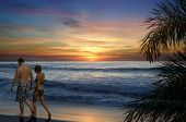 foto of beach sunset  - Couple walking along a tropical beach at sunset - JPG