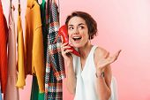 Image of a beautiful woman stylist posing isolated over pink wall background near a lot of clothes h poster