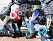 Without Hope - a homeless man bows his head as he sits amongst the only items he owns in a shopping