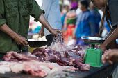 Vietnamese Butcher With A Piece Of Pig Meat. Meatman Cutting Pig Snout In A Food Market In Sapa, Lao poster