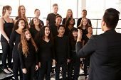 Male And Female Students Singing In Choir With Teacher At Performing Arts School poster
